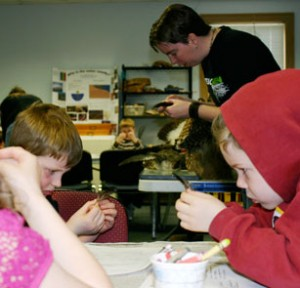 Students and teacher closely examining feathers.