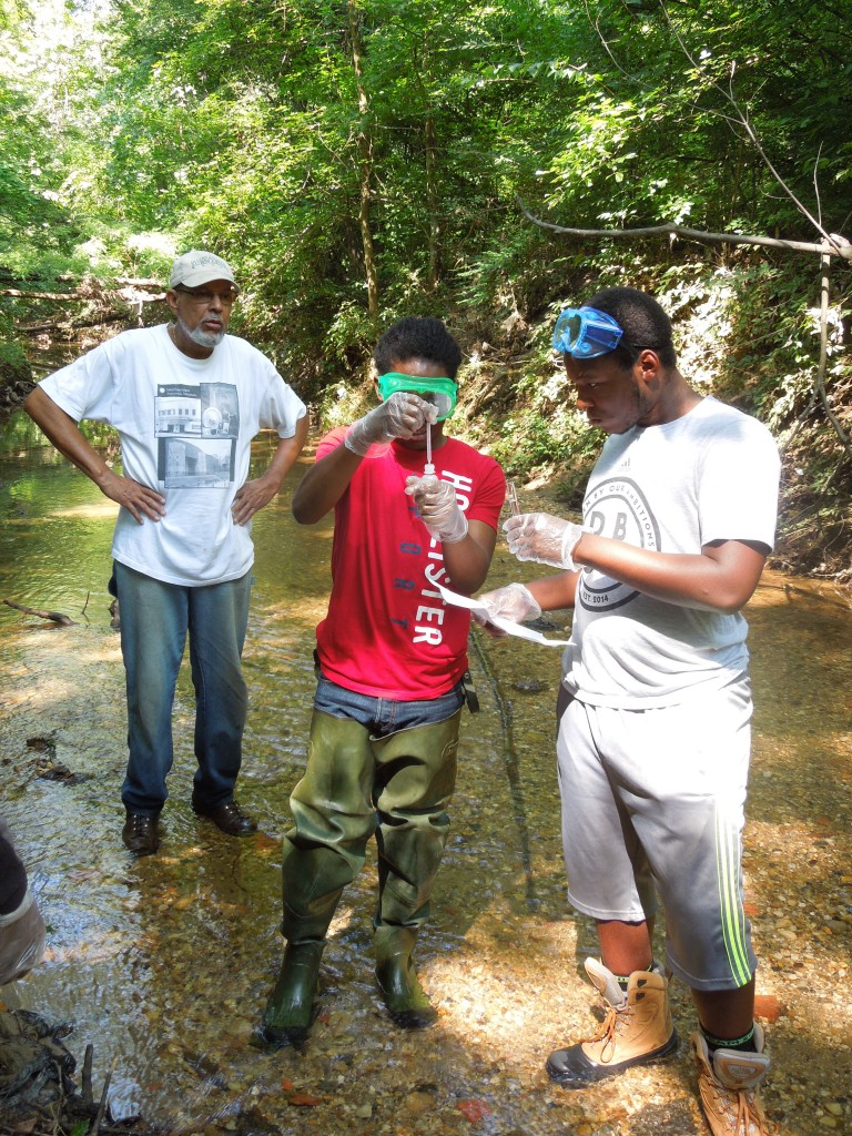 Tony Thomas (left) supervises while Donovan Eason (center) and DaWayne Walker run a chemical test on a water sample.