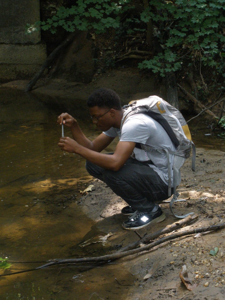 Kofi Henderson collects a water sample at Pope Branch of the Anacostia River.