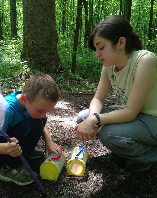 Intern Addie Schlussel, a rising junior at St. Mary's College of Maryland, and 6-year-old Luke discuss why some insects live in the dirt.