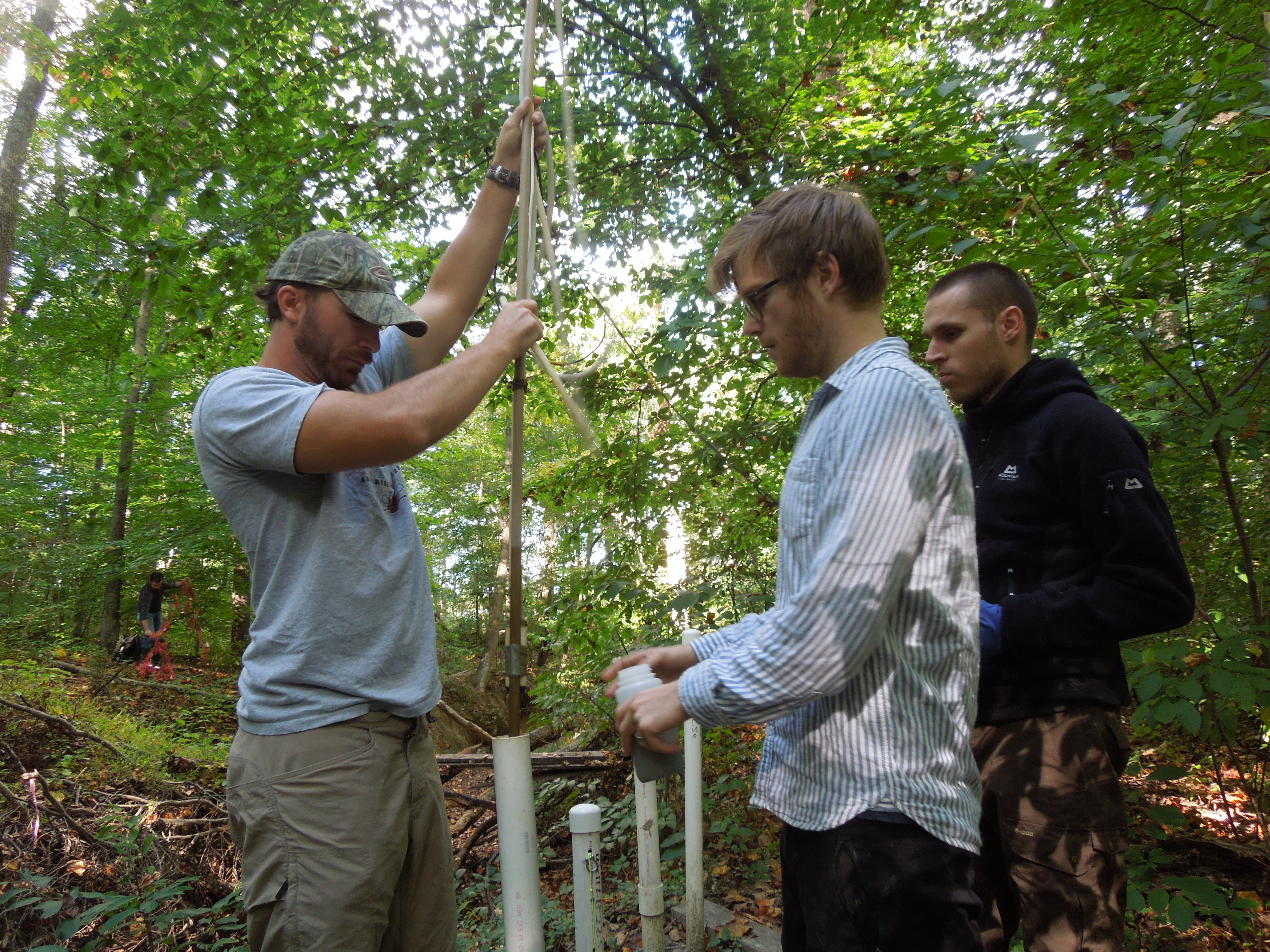 Image: Technician Max Ruehrmund, postdoc Joshua Thompson and intern Jan Kreibich take a water sample from one of the Muddy Creek piezometers. (Credit: SERC)