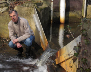 Image: Tom Jordan beside a V-shaped weir that tracks nutrients in a SERC stream. (SERC)