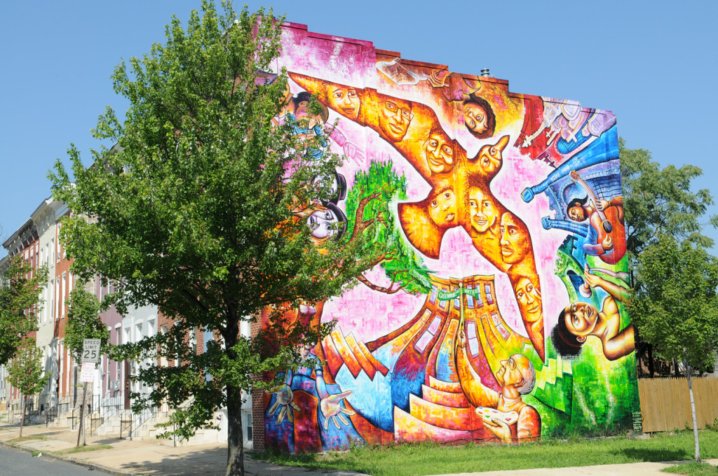 Wall art on a Baltimore building: A golden bird full of faces rises from a tree and a city building.
