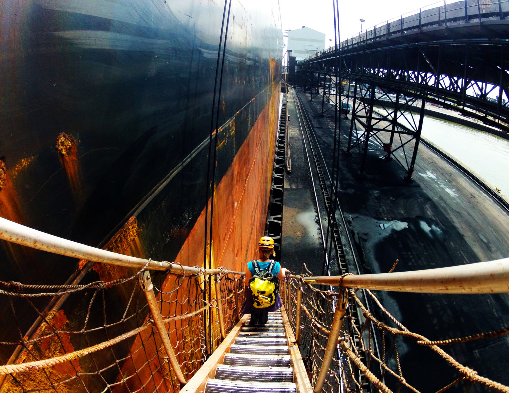 Woman descends gangway of large cargo ship.