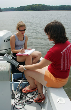 Two summer interns in a boat measuring the water's dissolved oxygen.