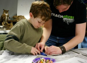 Teacher and student work with a clay modely of a bird feather.