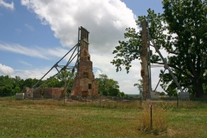 Photo of the ruins of two brick chimneys being supported by huge braces.
