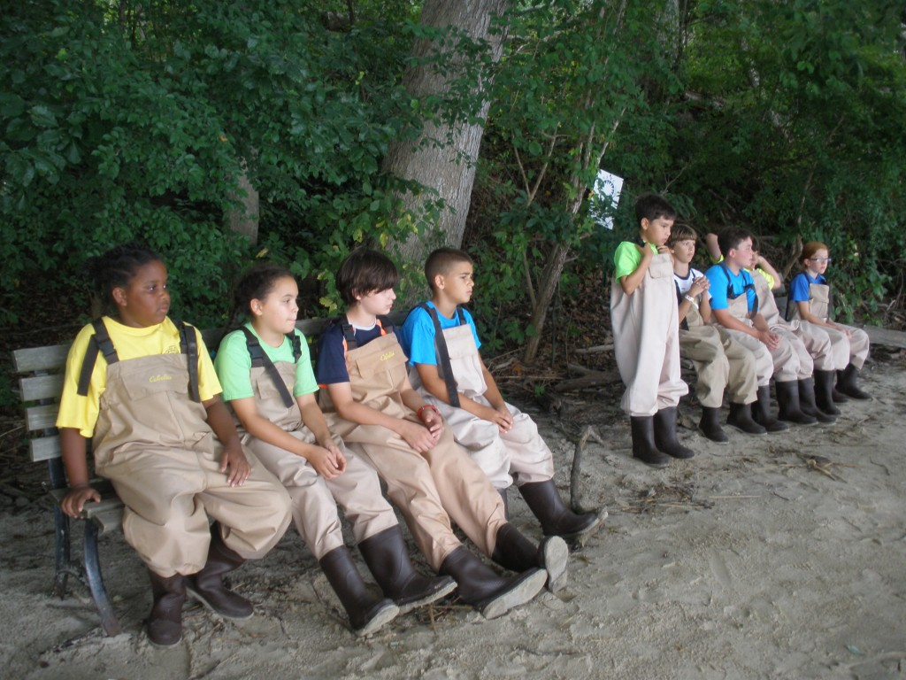 The campers listen to instructions about how to use the seine nets.
