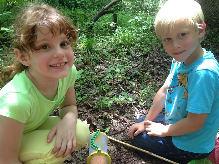 7-year-old Vivian and 6-year-old Gordon kneel in the dirt looking for insects.