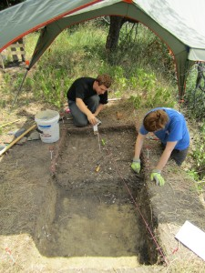 Scientist and intern excavate a shell midden