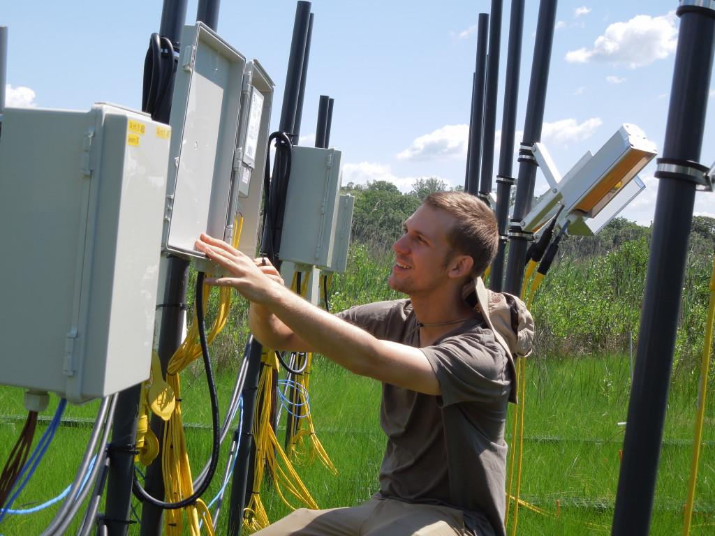 Joe Dawson kneels by a control box on marsh