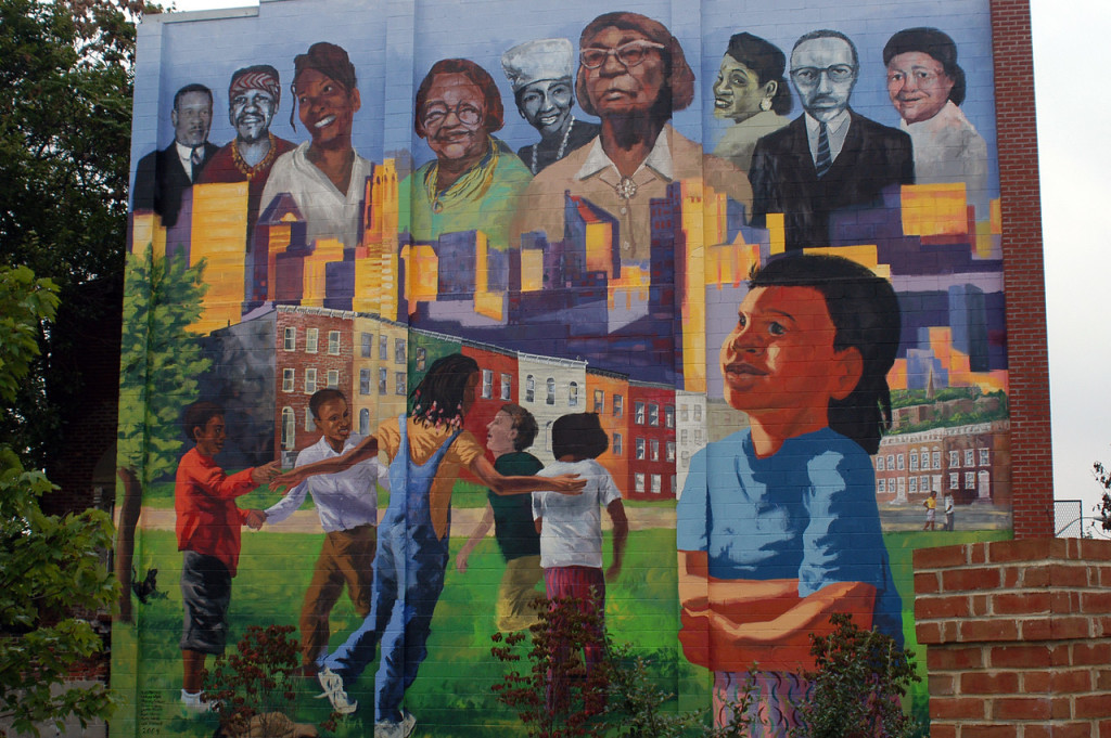 Painting of adults and children on a brick wall in Baltimore.