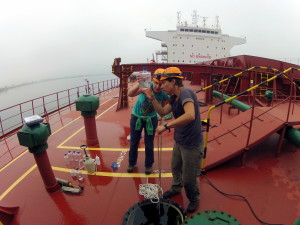 Two scientists look at water sample on ship.