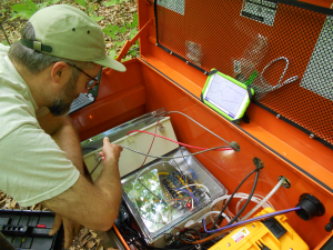 A scientist looks into an orange container with tubes and electrical equipment