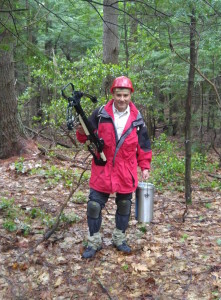 A researcher holds a crossbow and metal container of liquid nitrogen in a forest.