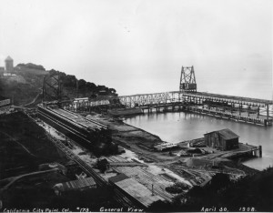 A large trestle and construction equipment in and around a cove.