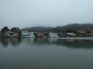A view across water with houses, a mountain, and hanging mist.