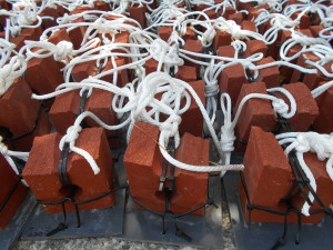 Bricks are zip-tied to grey plastic squares. Ropes are tied to the tops of the bricks.