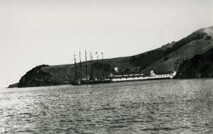 Old ships sit moored near a white warehouse in a cove with land rising up behind them.