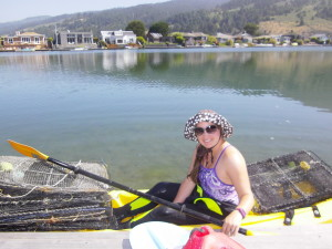 A researcher sits in a kayak with metal crab traps on the front and the back. She smiles into the camera.