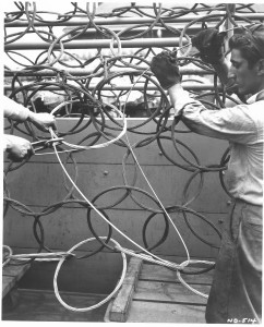 Two workers integrate a circular section of cable into a net with many other similar circular sections of cable.