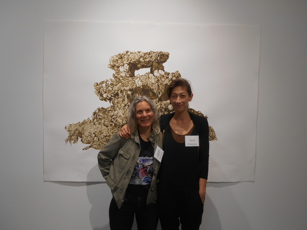 Two women stand in front of a painting on white wall.