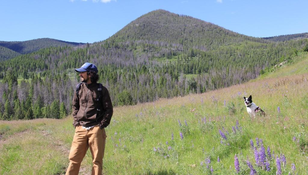 Joe La Manna on plain beside mountains with dog