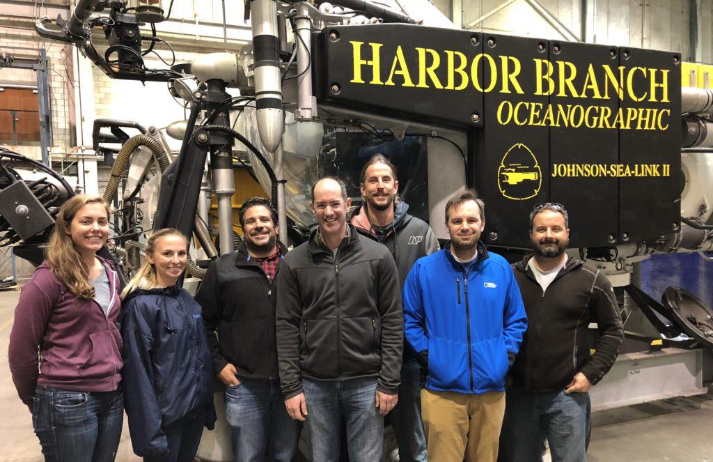 Seven scientists pose in front of Harbor Branch Oceanographic equipment