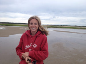 Sarah Donelan in red hoodie on sandy beach